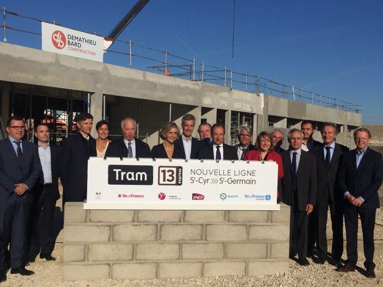 Personnels d'île-de-France mobilités derrière un petit mur et une plaque pour le lancement des travaux du Tram 13 express